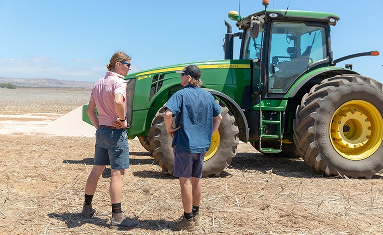 two-men-standing-in-paddock-with-tractor