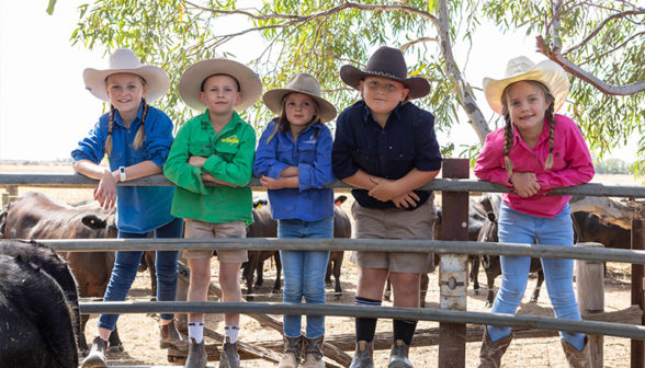 five-farming-children-standing-on-a-farm-fence